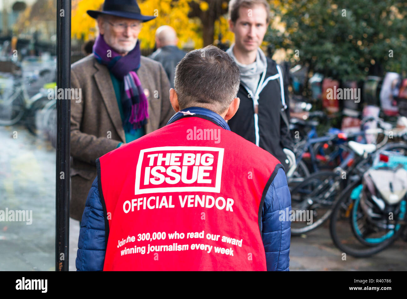 An official vendor of the Big Issue street newspaper on the streets of Cambridge, England, UK. - Stock Image