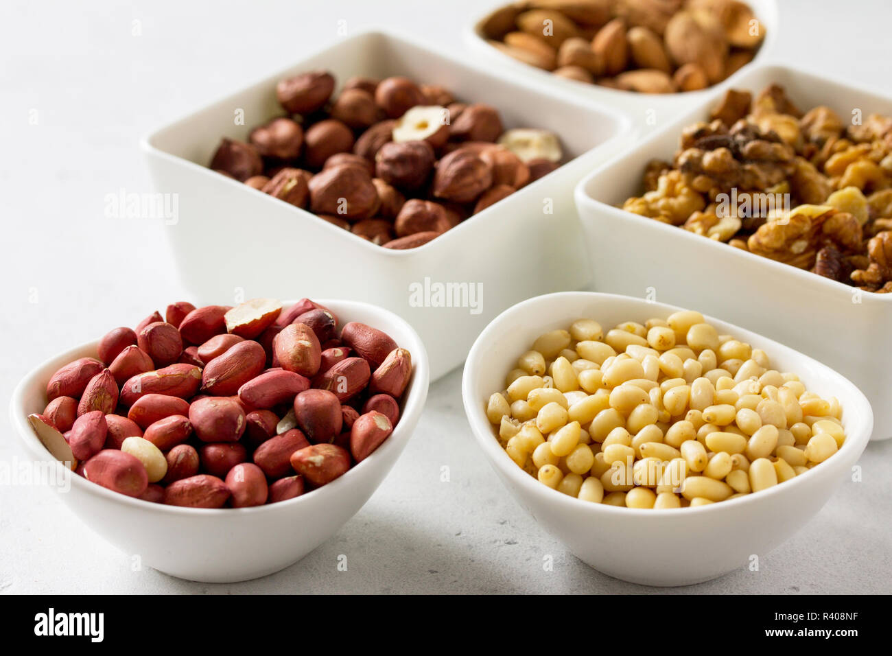 Various nuts in a ceramic bowl (walnut, almonds, pine nuts, hazelnuts) on a light stone table. The concept of a healthy dessert. - Stock Image