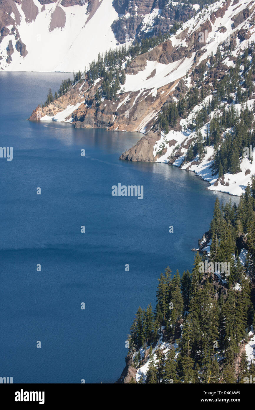 USA, Oregon, Crater Lake. Springtime snow lines crater rim. - Stock Image