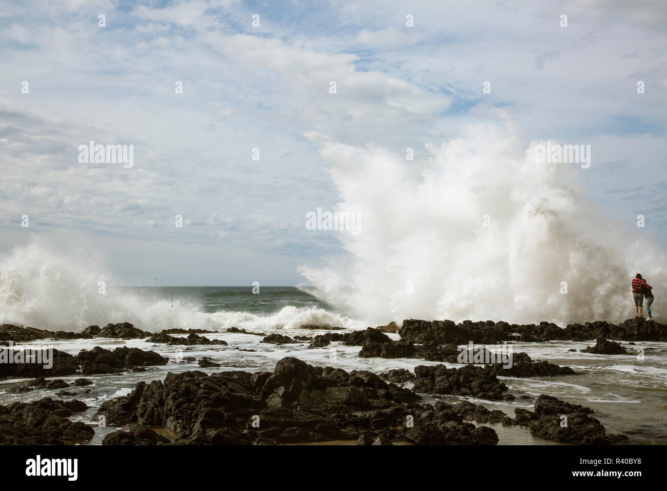 USA, Oregon, Cape Perpetua. Two girls and large wave. Credit as: Don Grall / Jaynes Gallery / DanitaDelimont. com - Stock Image