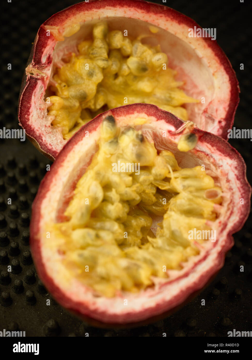Passionfruit halves showing the brightly coloured seeds, close up food photograph against a black background - Stock Image