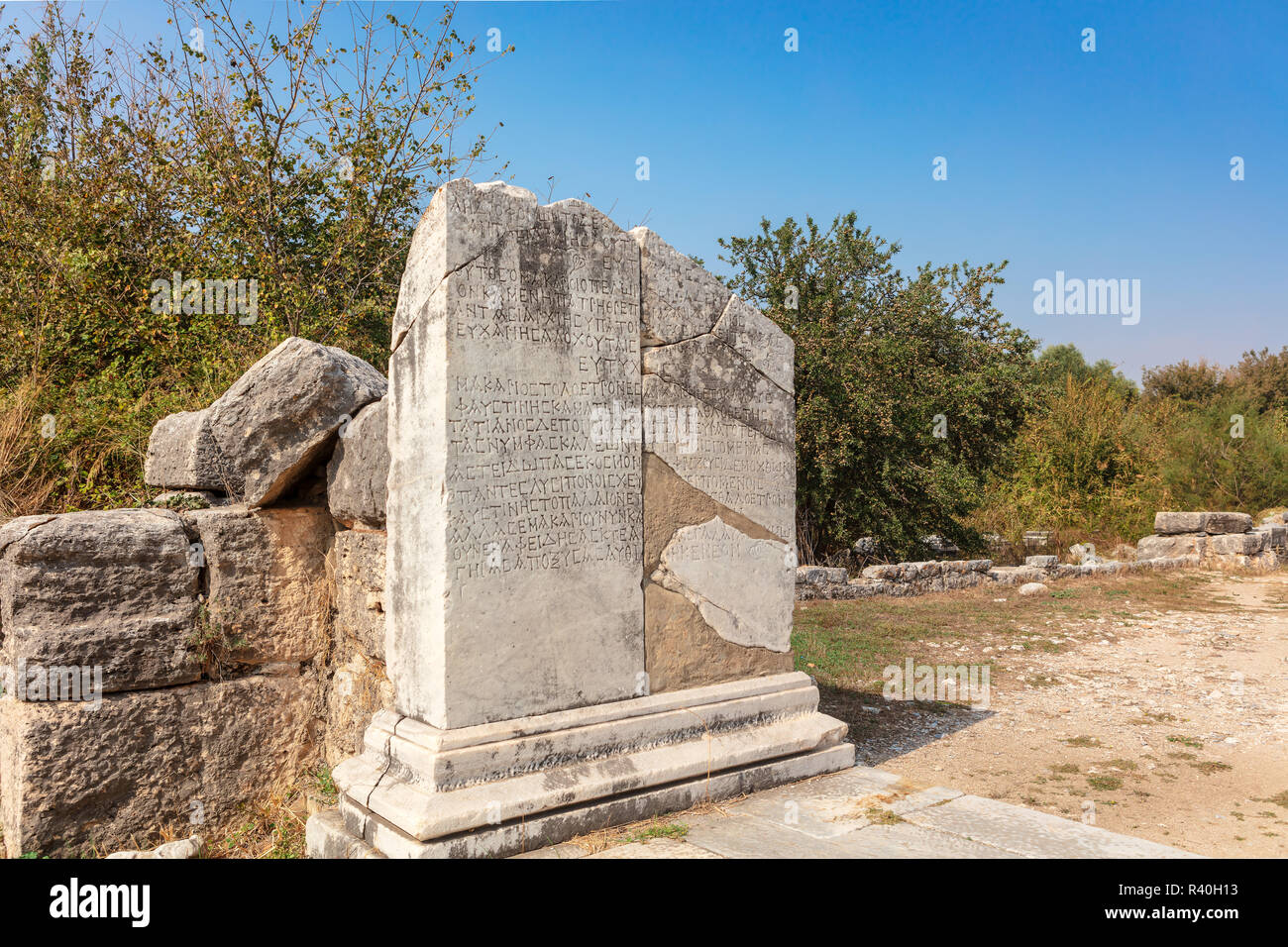 Detail of marble column with ancient Greek scripture and plinth at historic archaeological site of Miletus at Aydin province, Turkey. - Stock Image
