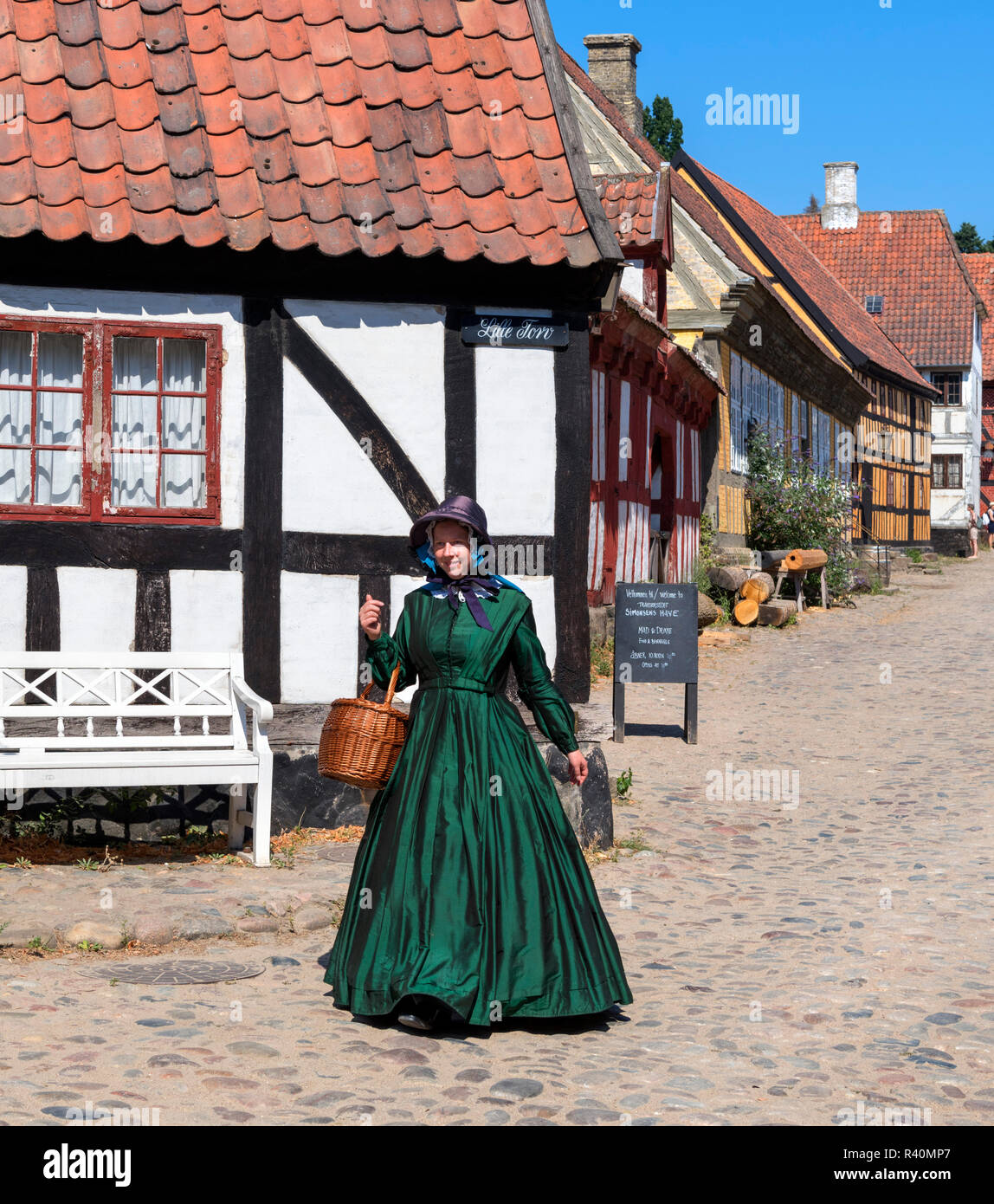 Woman dressed in period costume in The Old Town (Den Gamle By), an open air museum in Aarhus, Denmark - Stock Image