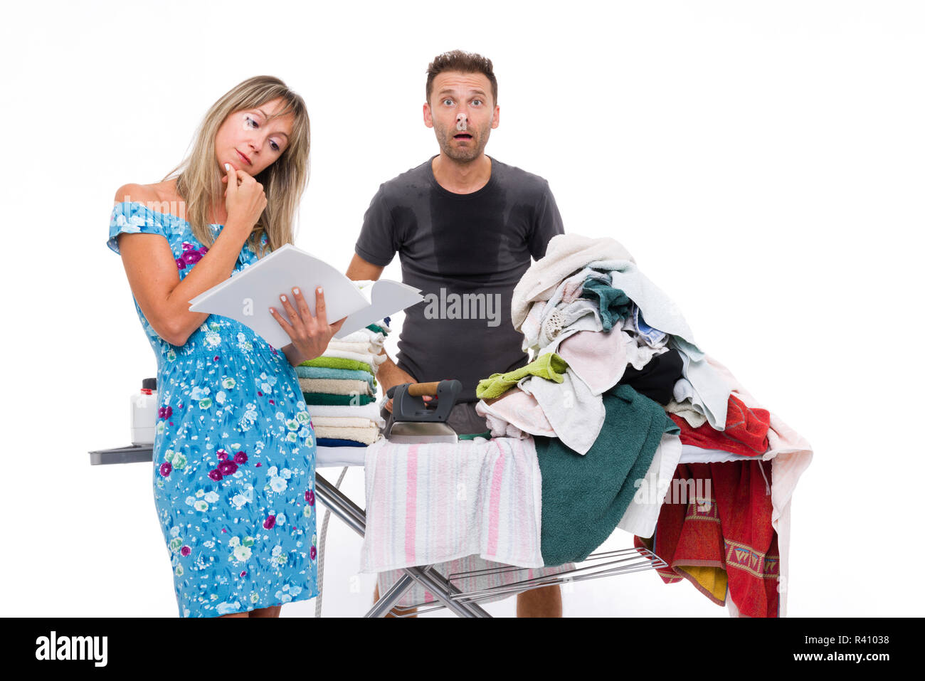 woman reading a newspaper, while a man shocked and sweating to iron - Stock Image