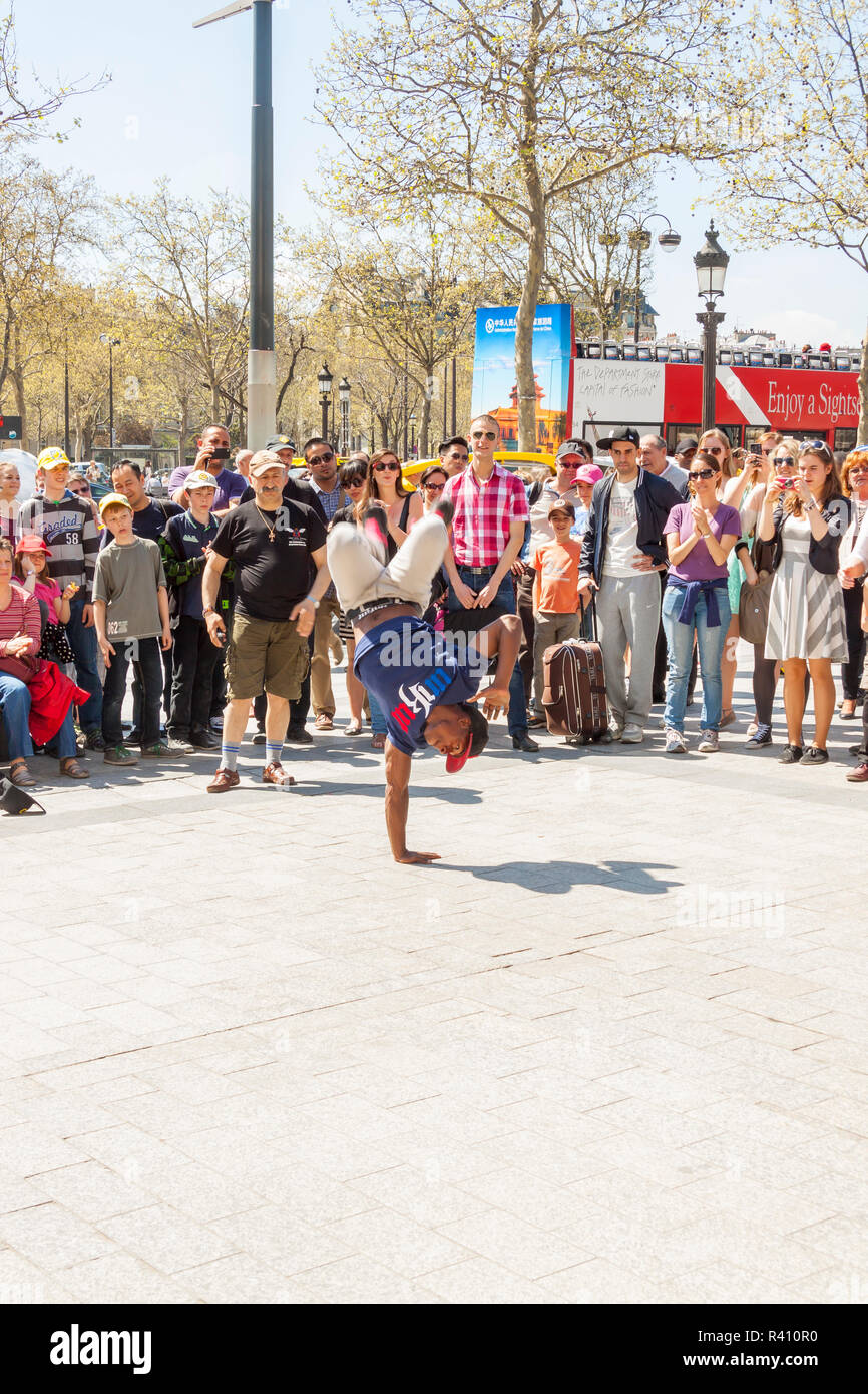 PARIS, FRANCE -  APRIL 25:B-boy doing some breakdance moves in front a street crowd, at Arch of Triumph on april 25, 2013 in Paris. Its popular form o - Stock Image