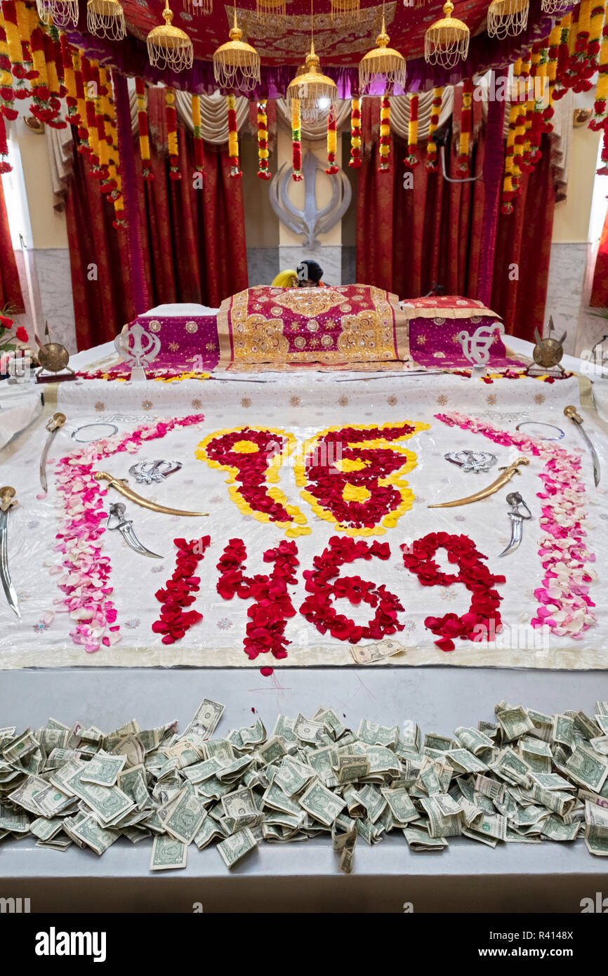 The altar at the Sikh Cultural Society temple in Richmond Hill, Queens, New York specially decorated for the birthday of Guru Nanak. - Stock Image