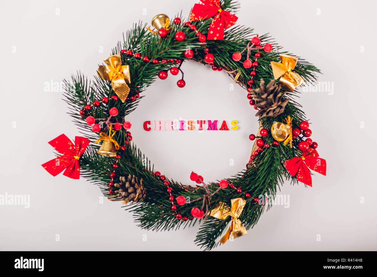 Christmas wreath with decoration on white background. Christmas title made of colorful wooden letters inside Stock Photo