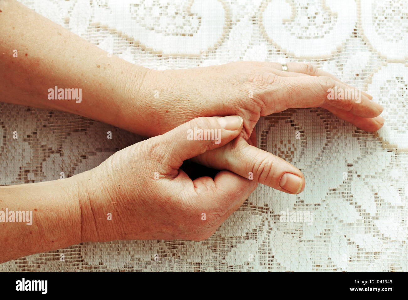 a woman has pain in the fingers,hands,and joints - Stock Image