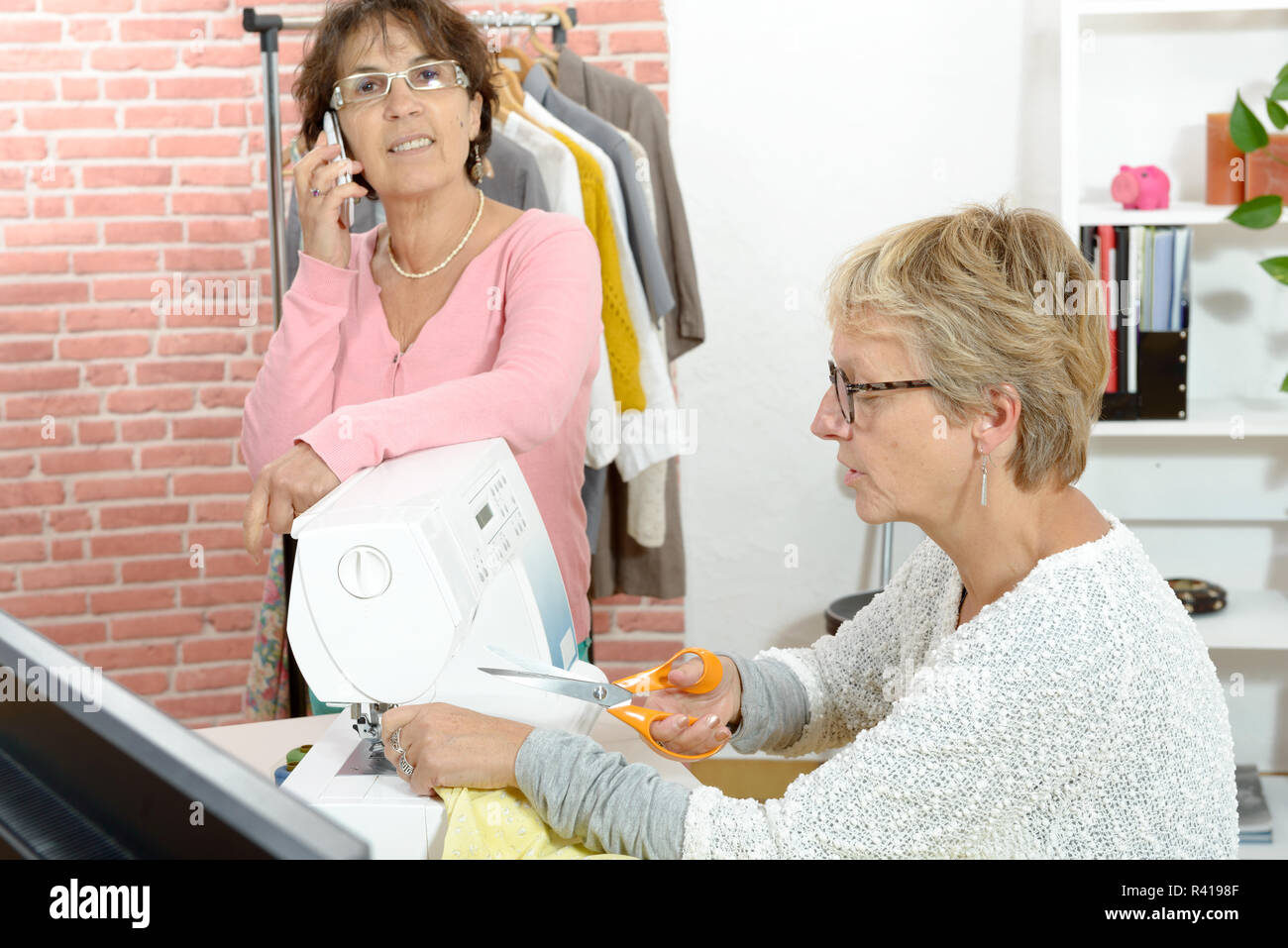 Two cheerful seamstresses working together in their  workshop Stock Photo