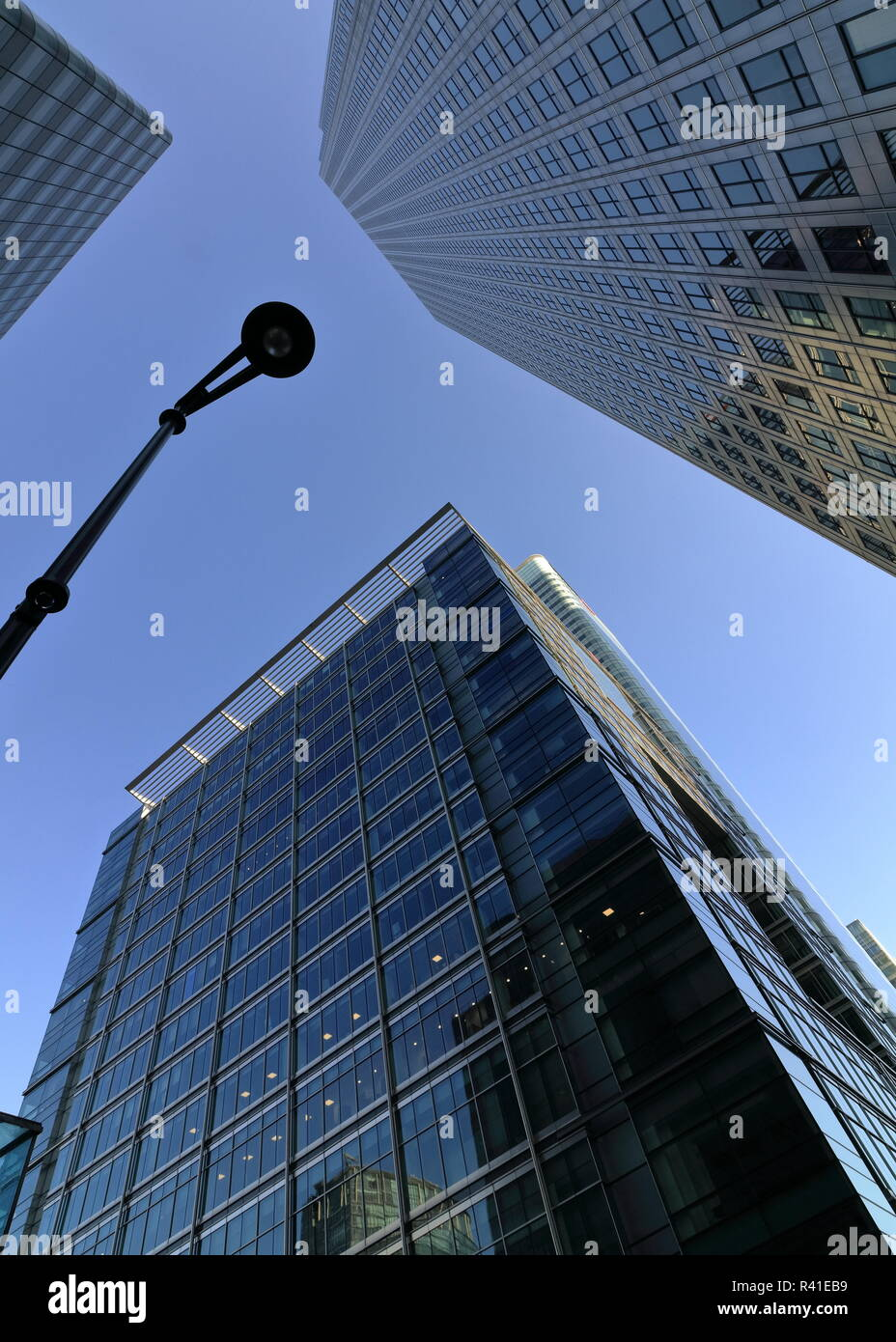 Looking up to the sky with tall skyscrapers around at Canary Wharf area in London.  Canada Square HSBS global asset. Business centre.  Sky reflections - Stock Image