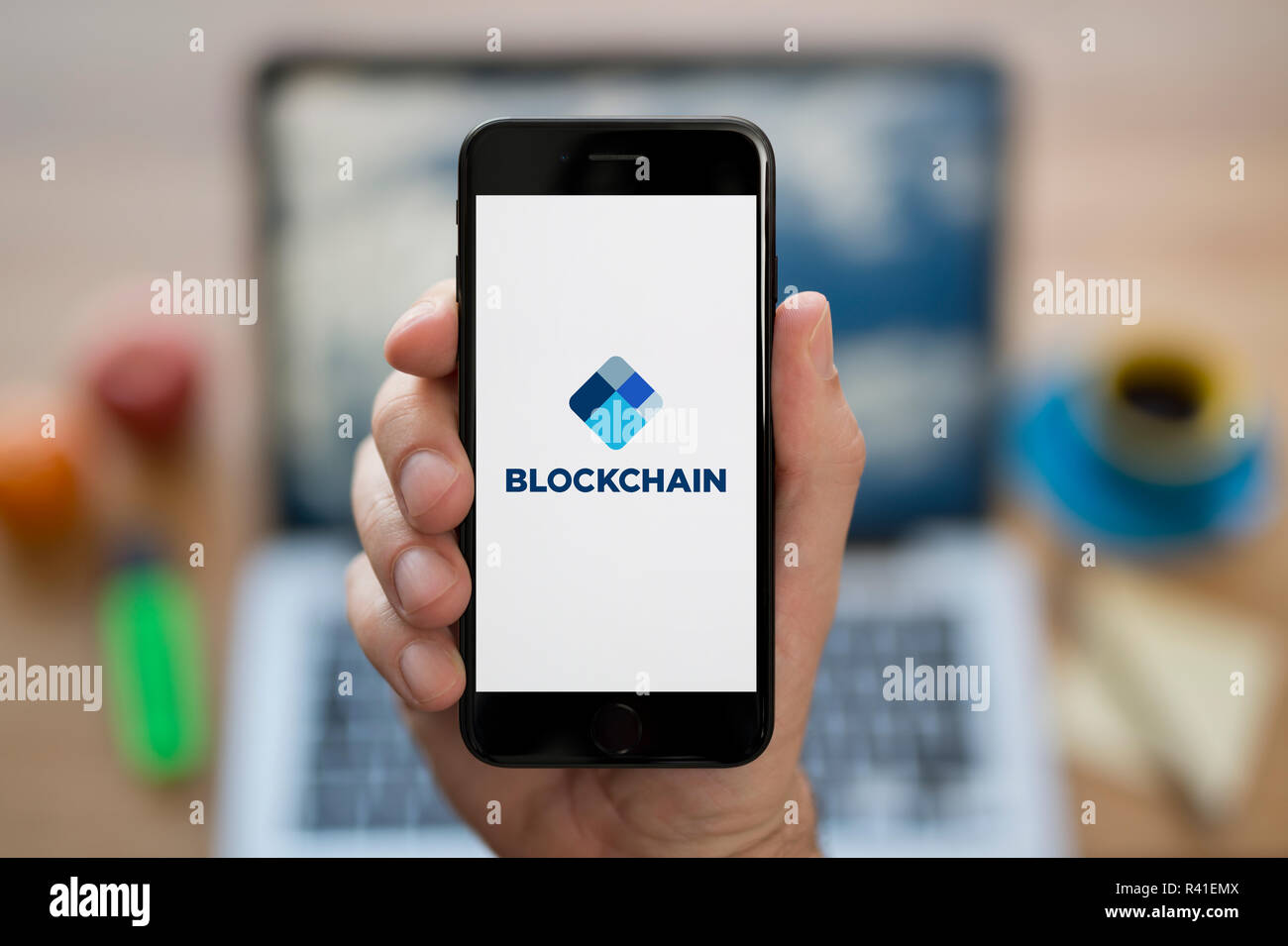 A man looks at his iPhone which displays the Blockchain logo, while sat at his computer desk (Editorial use only). - Stock Image