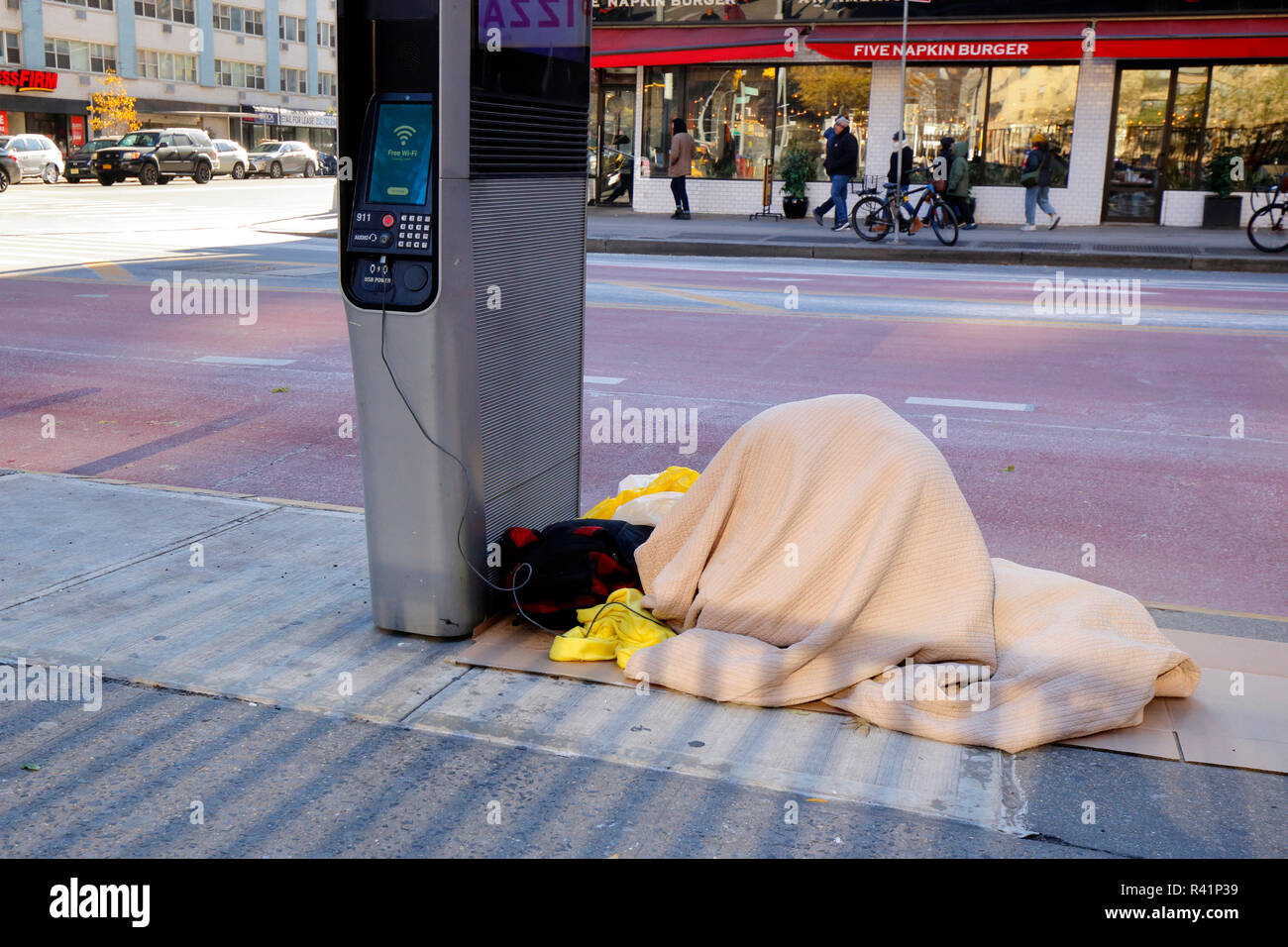 A person huddled under blankets near a free wifi and telephone kiosk in New York City - Stock Image