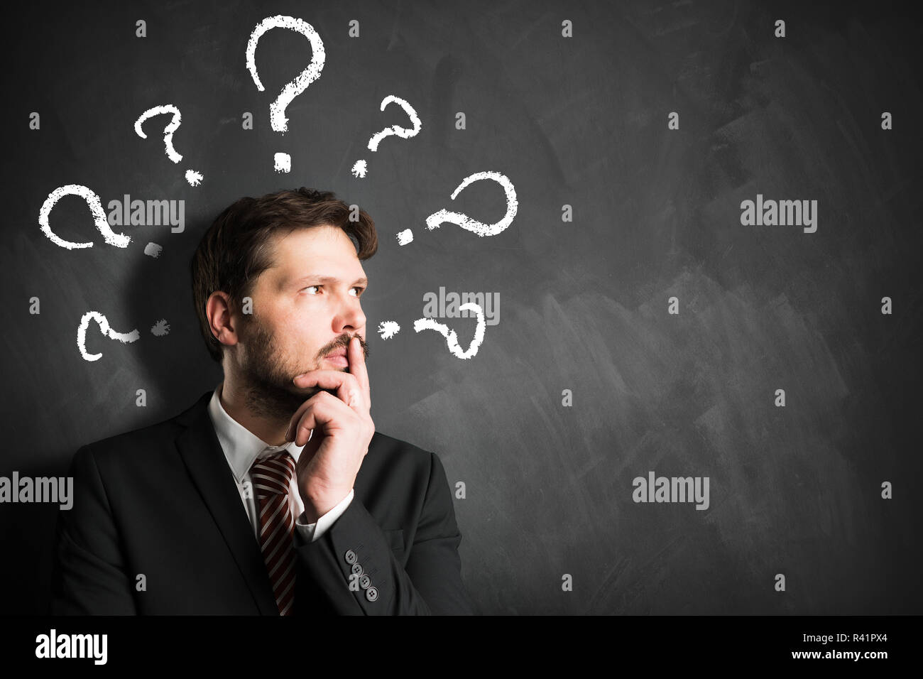 businessman having many questions symbolized as questionmarks on a blackboard over his head - Stock Image