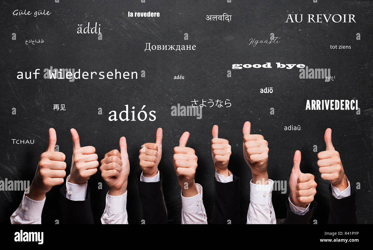 many thumbs up in front of a blackboard with a goodbye in many languages - Stock Image