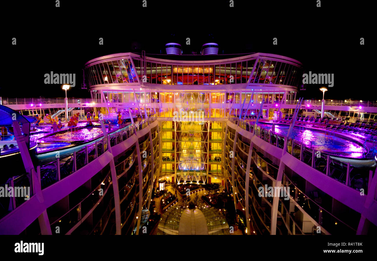 The lighted pool decks on Oasis of the Seas overlook the open, treed area called Central Park. - Stock Image
