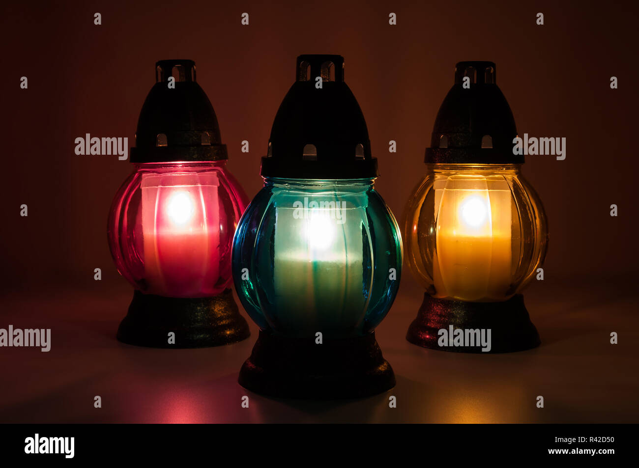 burning votive candles in the dark - Stock Image