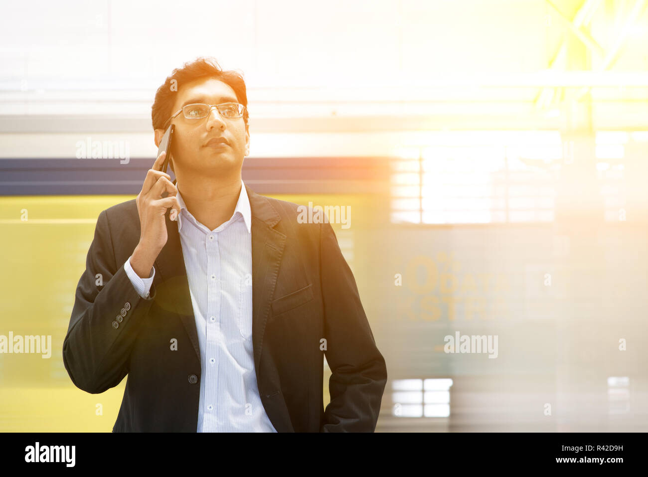 Indian businessman on the phone at railway station. Stock Photo