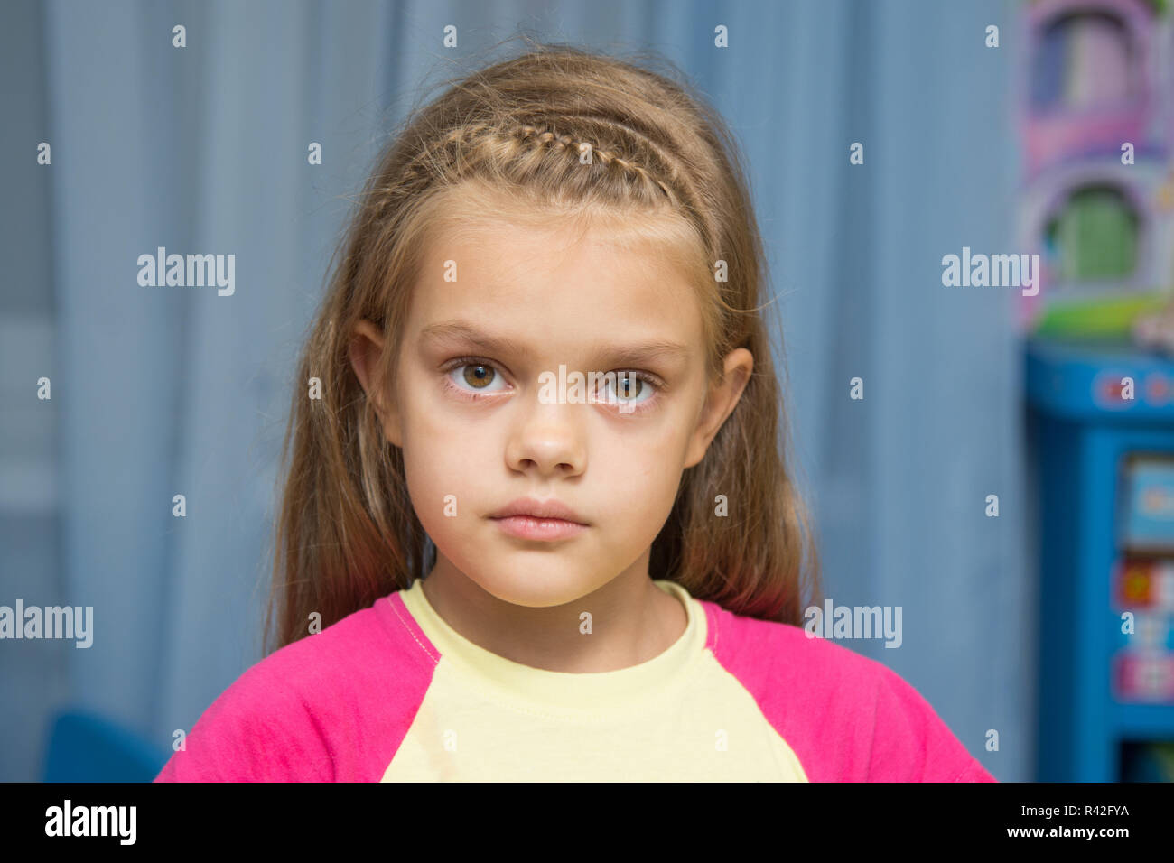 Upset five year old girl with tearful eyes - Stock Image
