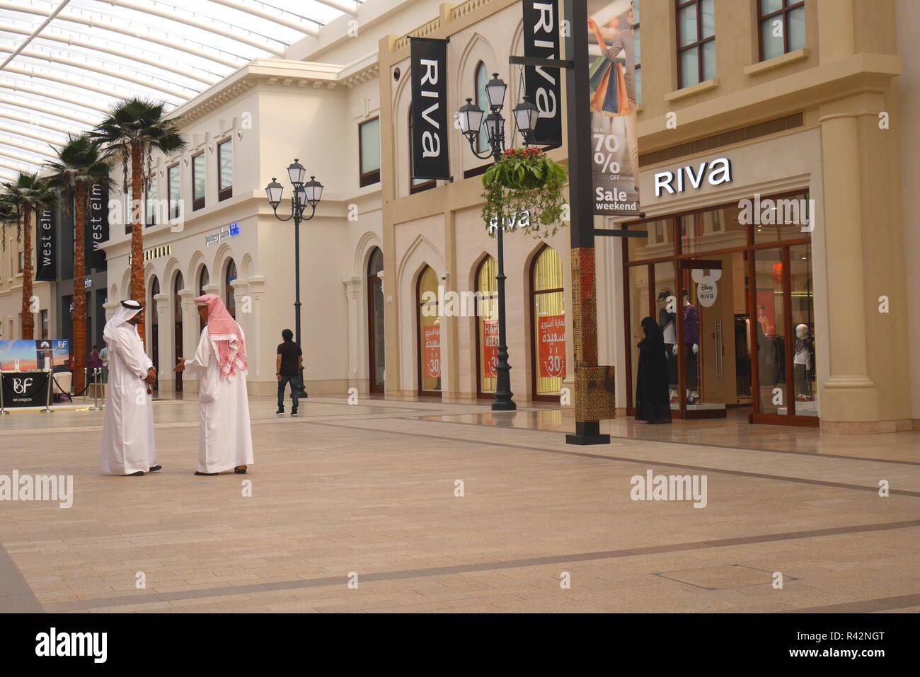 Two Bahraini men in dishdashas talking inside the Avenues shopping mall, located on Bahrain Bay, Manama, Kingdom of Bahrain - Stock Image