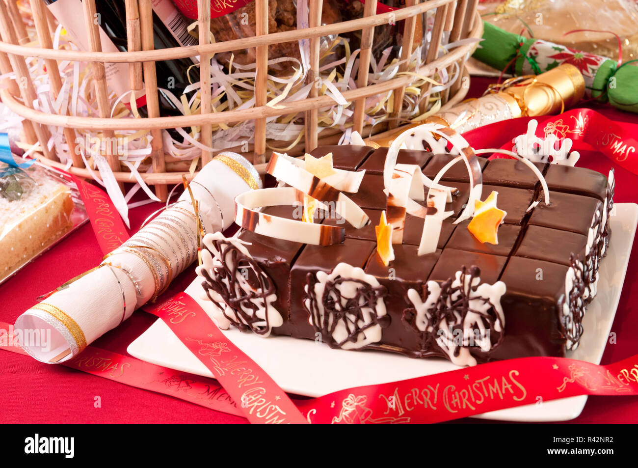 Christmas chocolate cake with a hamper basket at the background Stock Photo