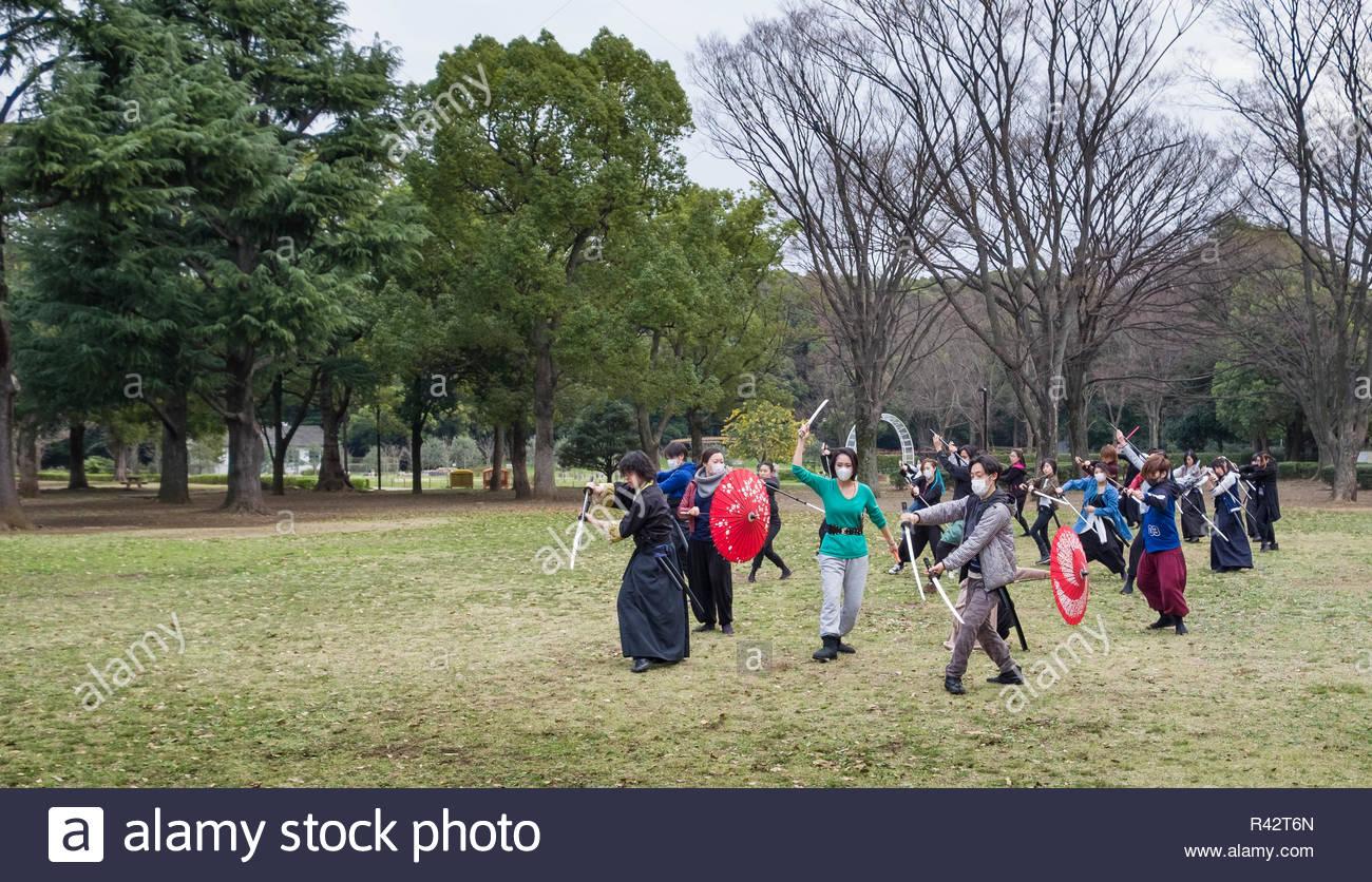 Group of people practicing choreographed movements with swords and umbrellas in Yoyogi Park, Shibuya, Tokyo, Honshu, Japan - Stock Image