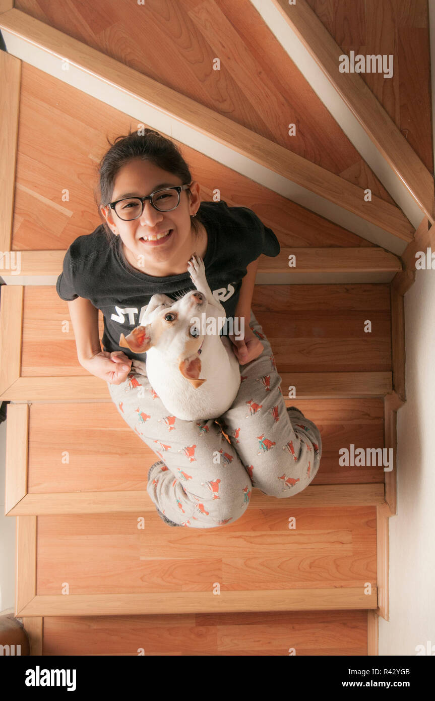 Pets in the home as family member. Teenager seatted on stairs palying with her dog and ready for a portrait photography - Stock Image
