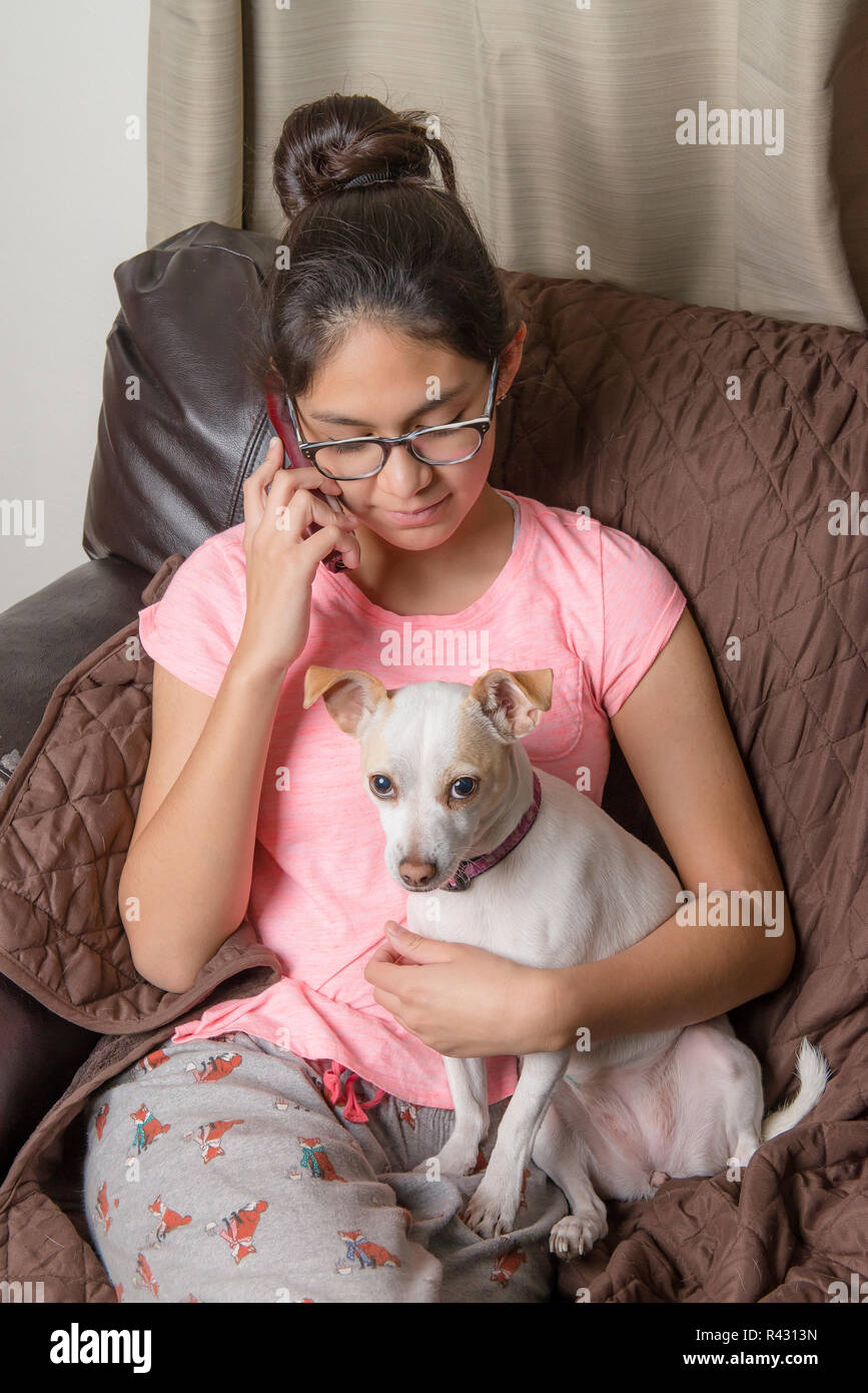Pets in the home as family member. Latin Mexican teenager making a phone call while hugging her dog, inside home. - Stock Image