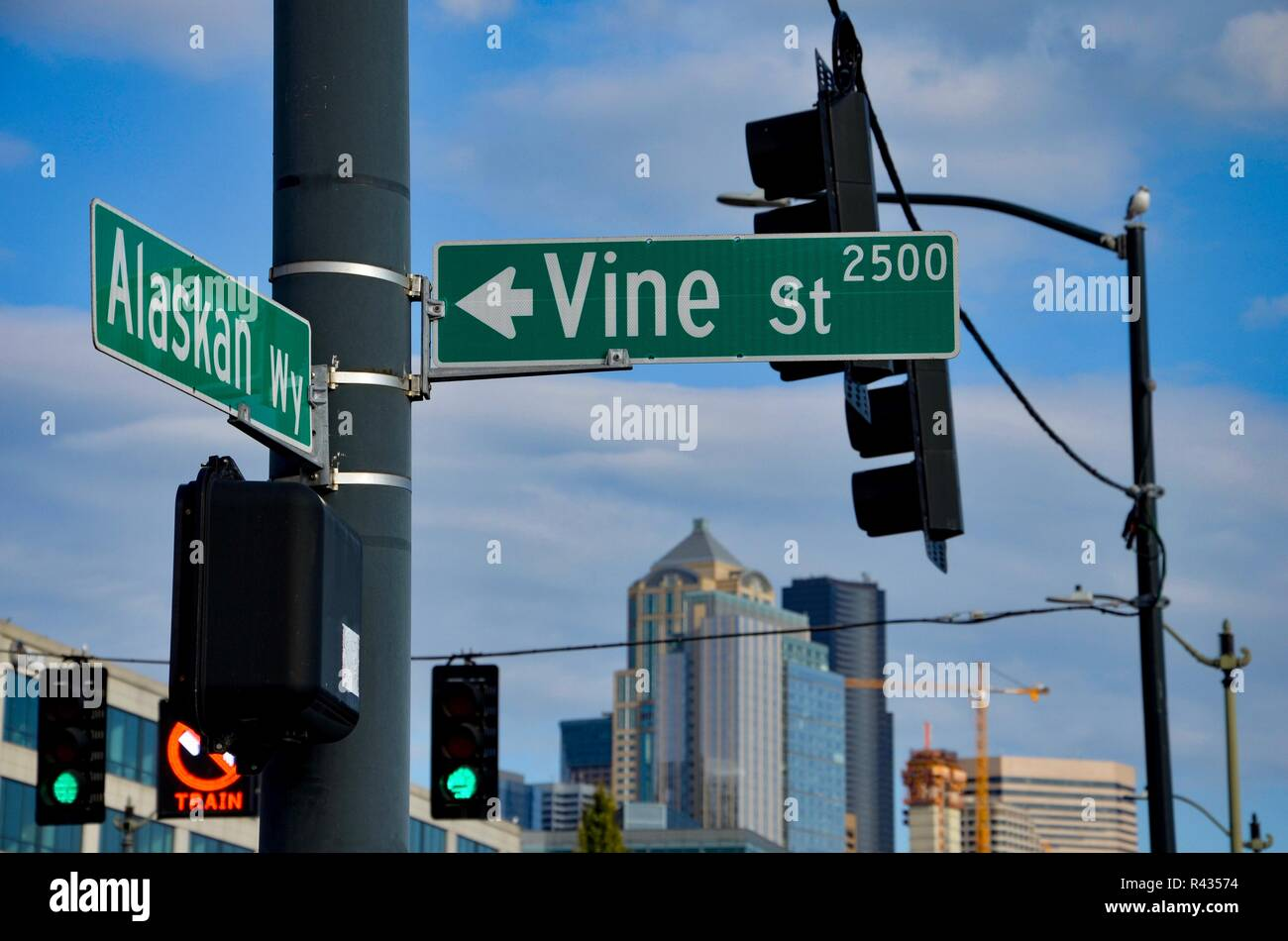 Green street sign in Seattle about Vine Street and Alaskan Way, Washington state, traffic lights, blurred background with buildings - Stock Image