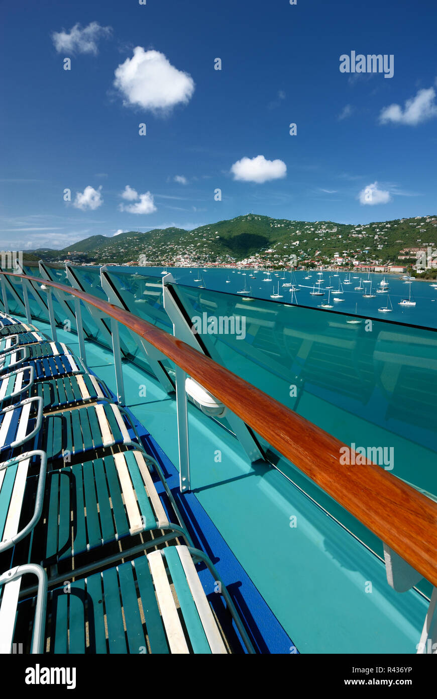 Lounge chairs along the railing of Royal Caribbean's Adventure of the Seas, overlooking St. Thomas, Virgin Islands. - Stock Image