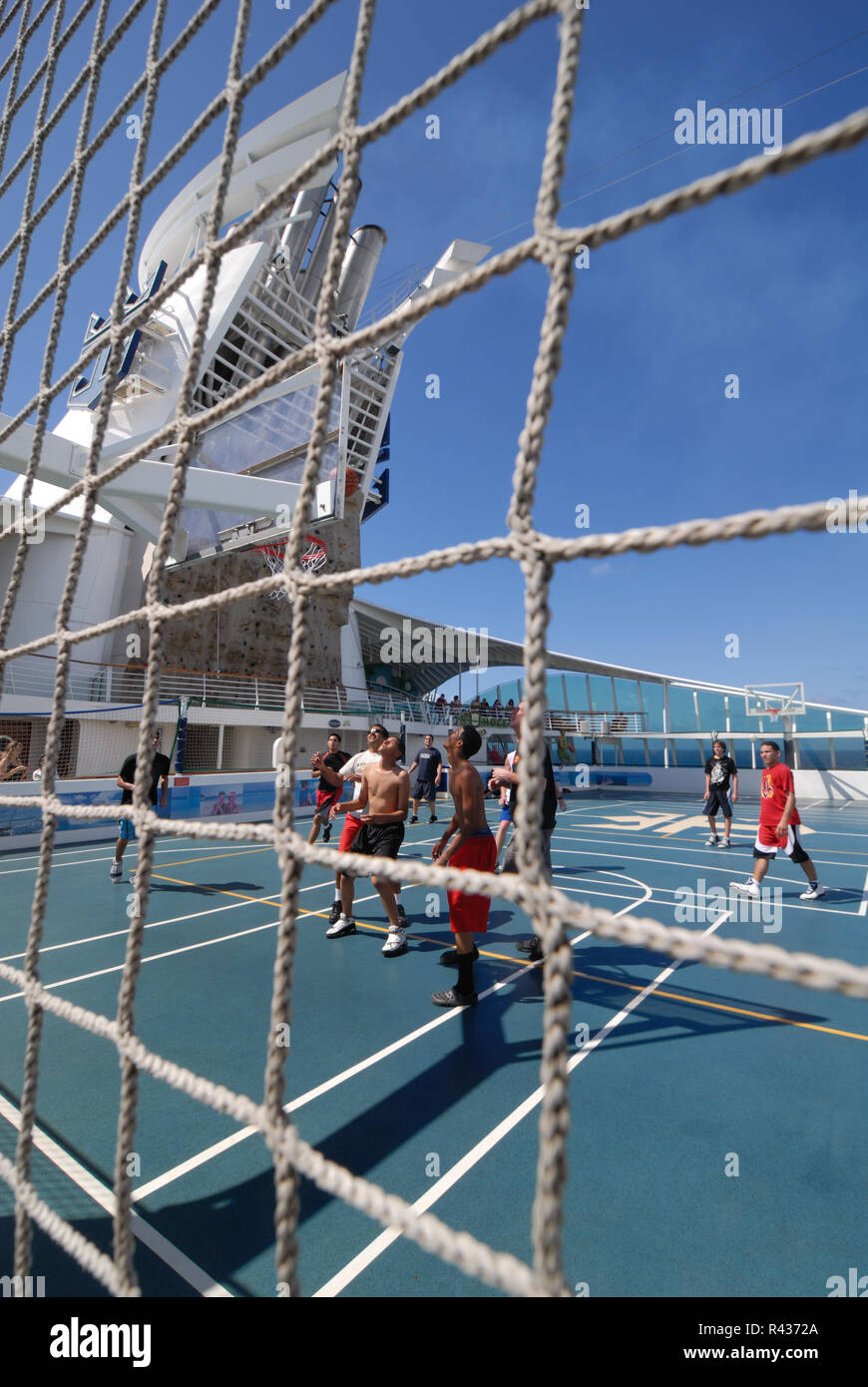 Young men play basketball on the sports deck of Adventure of the Seas cruise ship. - Stock Image