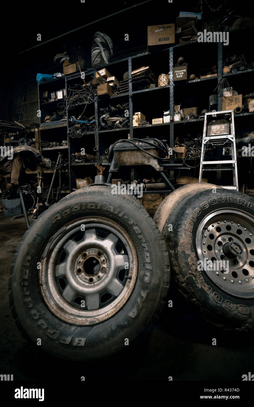 Tires are at the forefront of this scene in a darkly lit machine shop. - Stock Image