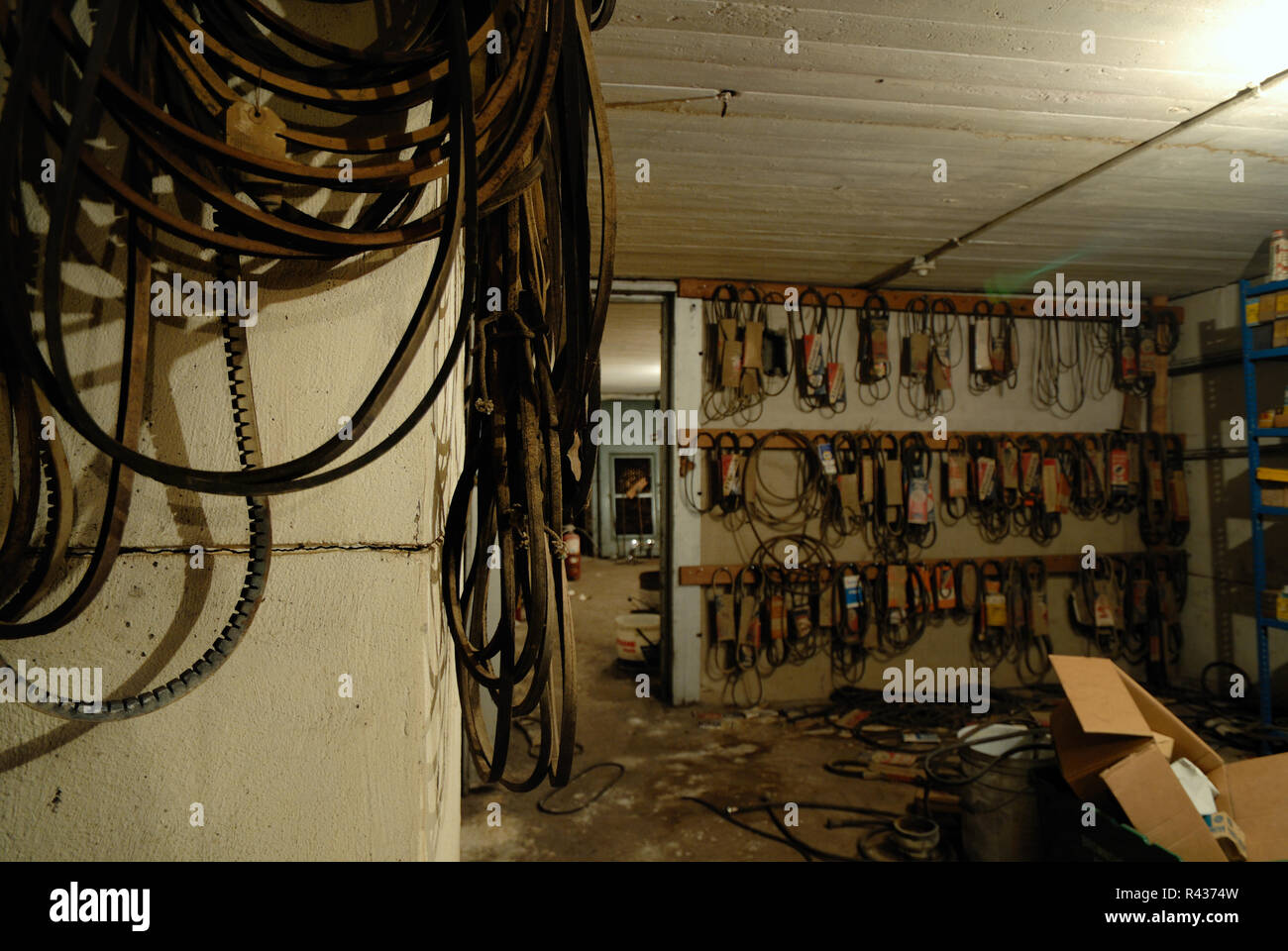 Many fan belts hang on the walls in a darkly lit warehouse basement Stock Photo