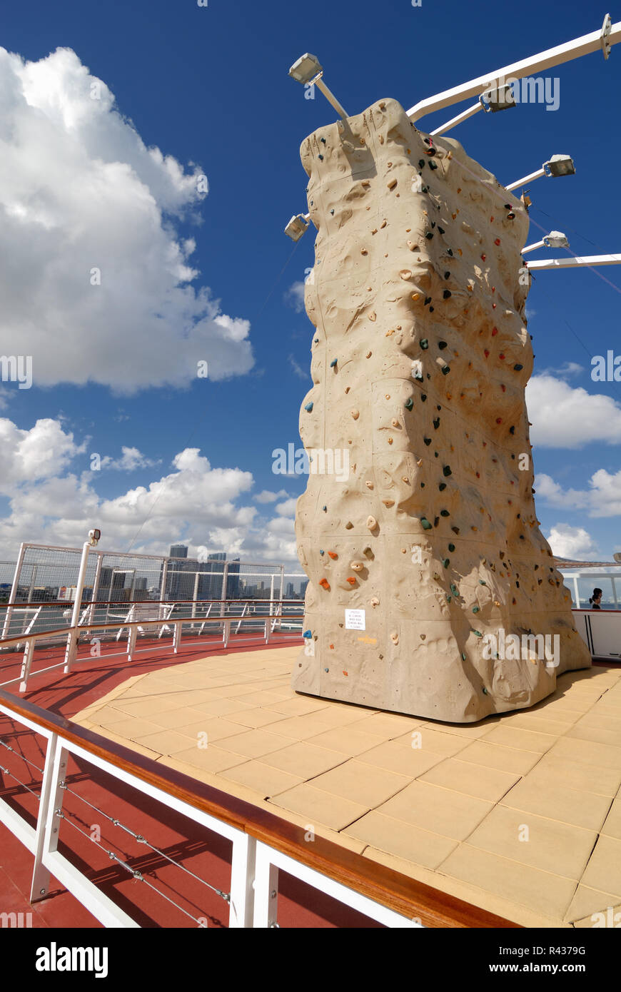 The rock climbing wall on the upper level sports deck of the Majesty of the Seas cruise ship.  The Miami, Florida skyline can be seen in the backgroun - Stock Image