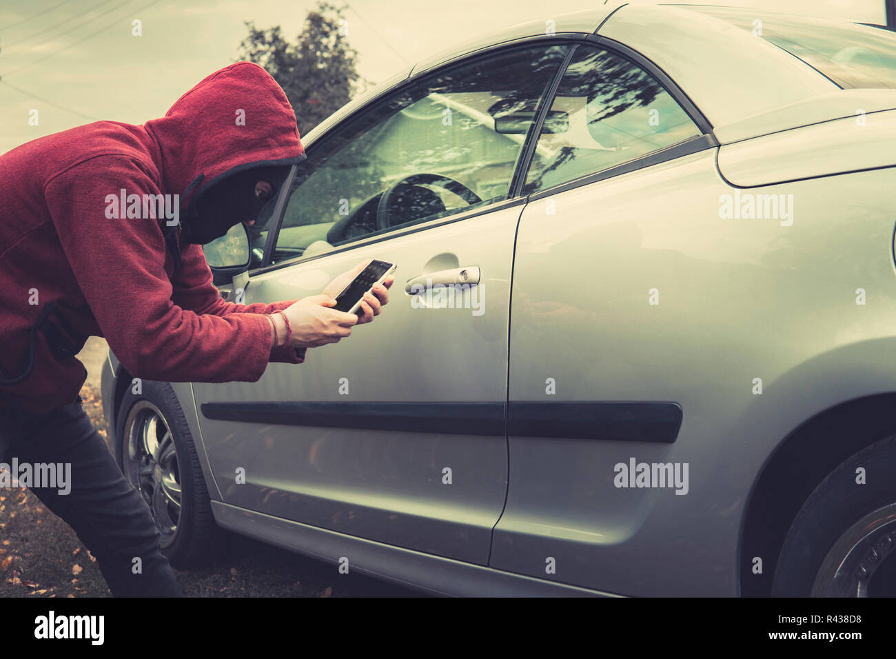 Side view of young criminal in black balaclava and hoodie holding smartphone and trying to interact with car by mobile application. Unknown person tri - Stock Image