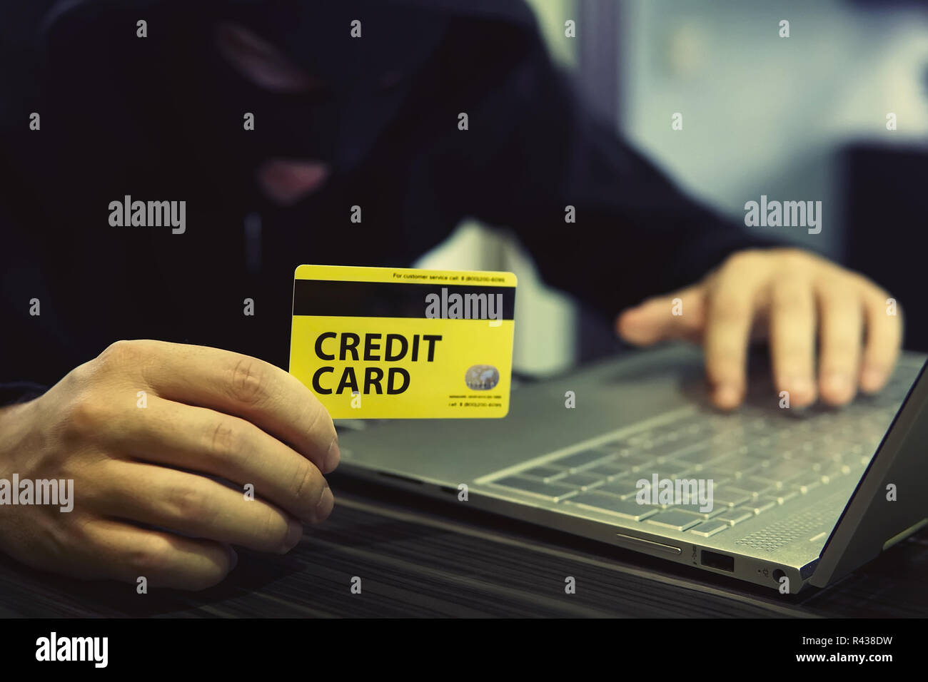 Unknown person uses computer and credit card to commit cyber crime. Computer trespasser uses internet to steal money. Drawing money from banking accou - Stock Image