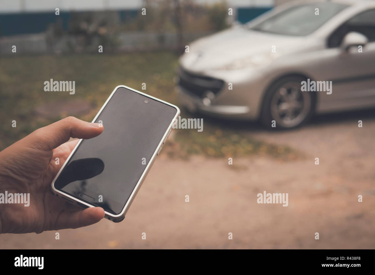 Person connects with smart car by phone application. Mobile app controls the work of a vehicle computer. Keyless car unlock by using cellphone. Vehicl - Stock Image