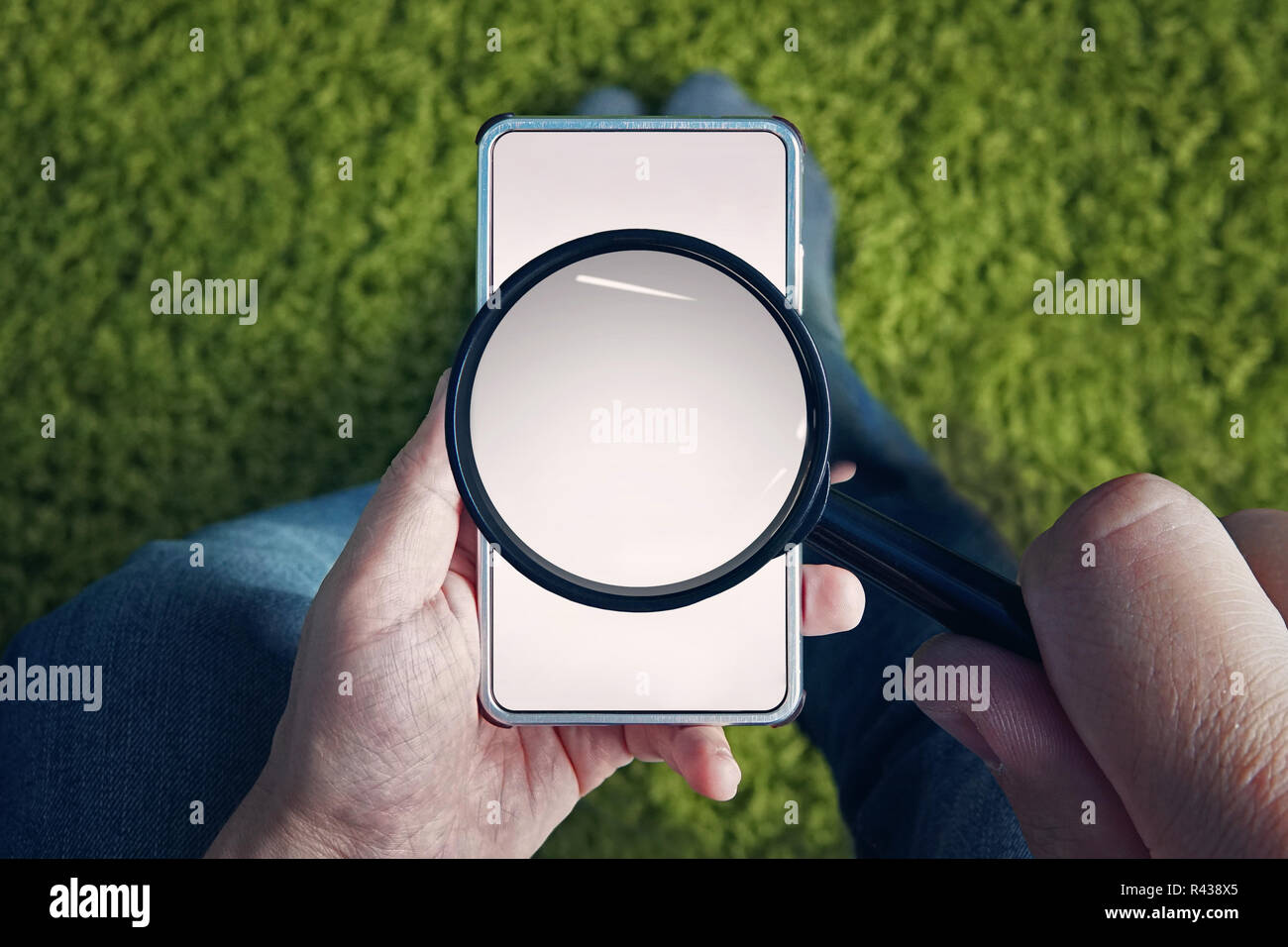 Top-down view to sitting man with blank smartphone and magnifying glass above its screen. Man holds magnifier to find something in mobile internet. Use of cell phone for searching information online. Stock Photo