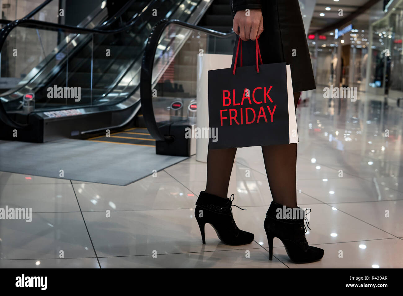season of autumn sales on black Friday. Girl carrying a shopping bag at Mall. Stylish slim ladies walking shopping bags in the store during shopping process, concept of consumerism, sale, rich life - Stock Image