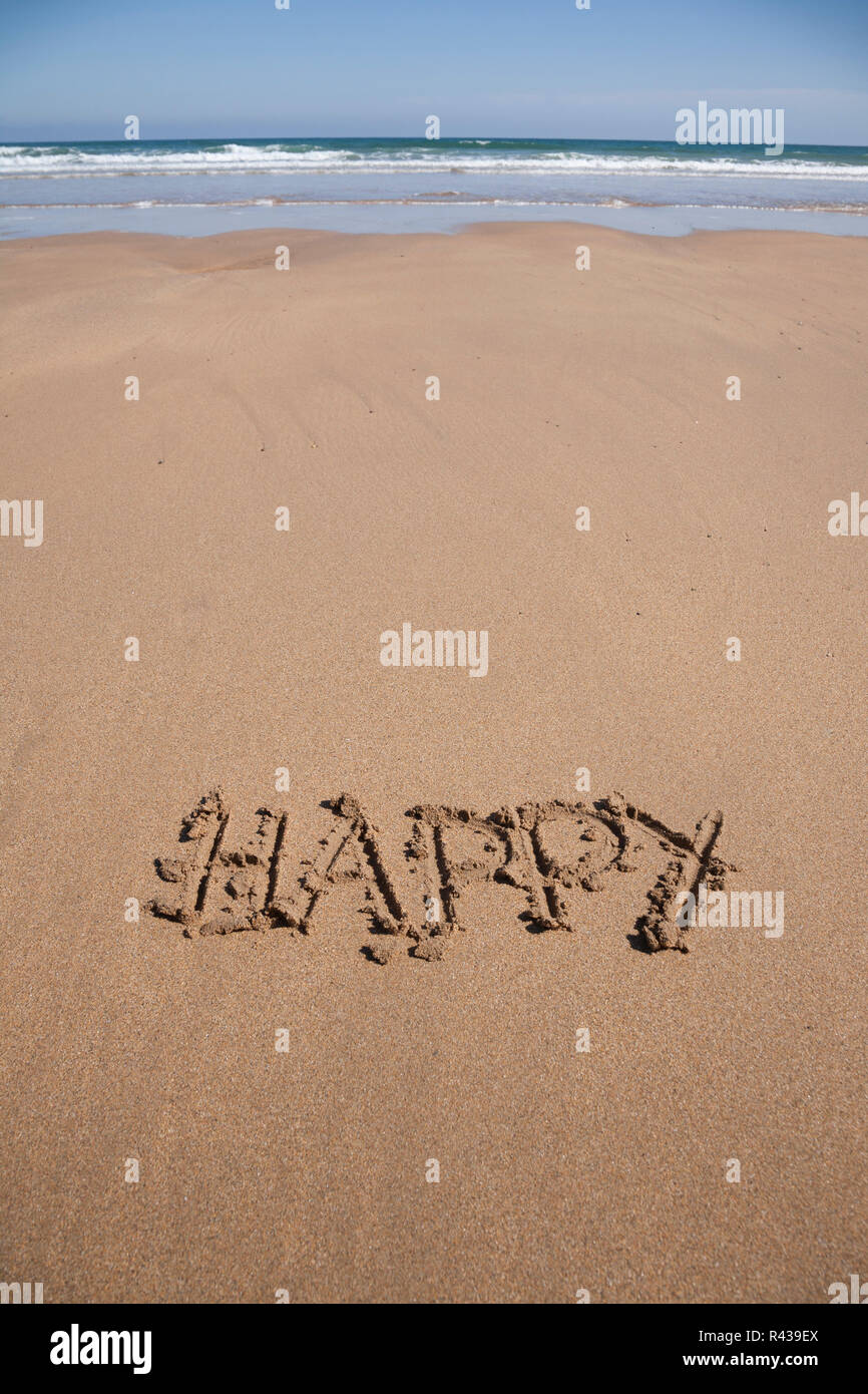 happy text in sand beach - Stock Image