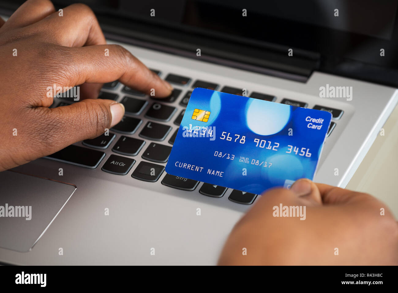 Person's Hand Using Debit Card While Shopping Online - Stock Image