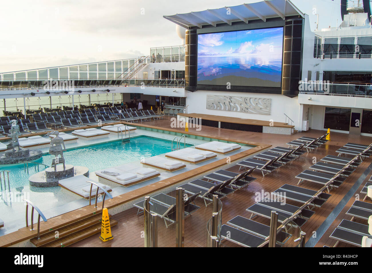 Outdoor deck with swimming pool, sun beds, video screen. CRUISE ship MSC Meraviglia, 8 October 2018. - Stock Image
