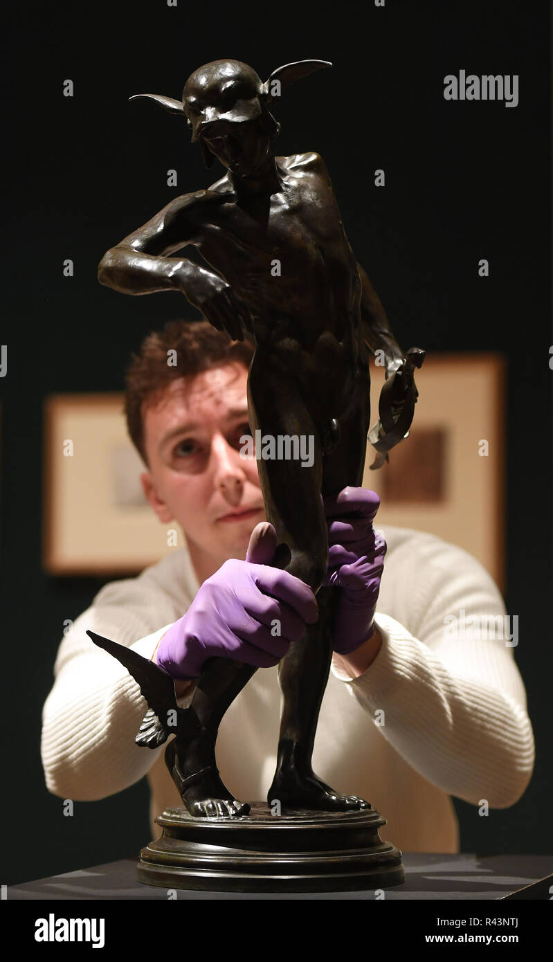 Gallery technician Tim Matthews inspects a bronze statue of Greek hero Perseus by Sir Alfred Gilbert, who famously sculpted the Eros statue in Piccadilly Circus, as it goes on display in the 'Collecting and Giving: Highlights from the Sir Ivor and Lady Batchelor Bequest' exhibition at the Fitzwilliam Museum in Cambridge. - Stock Image