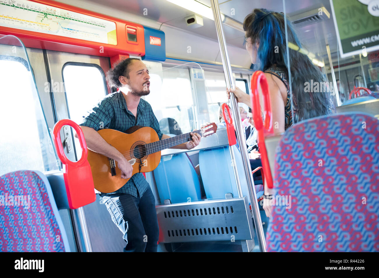 Man and woman performing a duet on a train headed for Lisbon, Portugal. - Stock Image