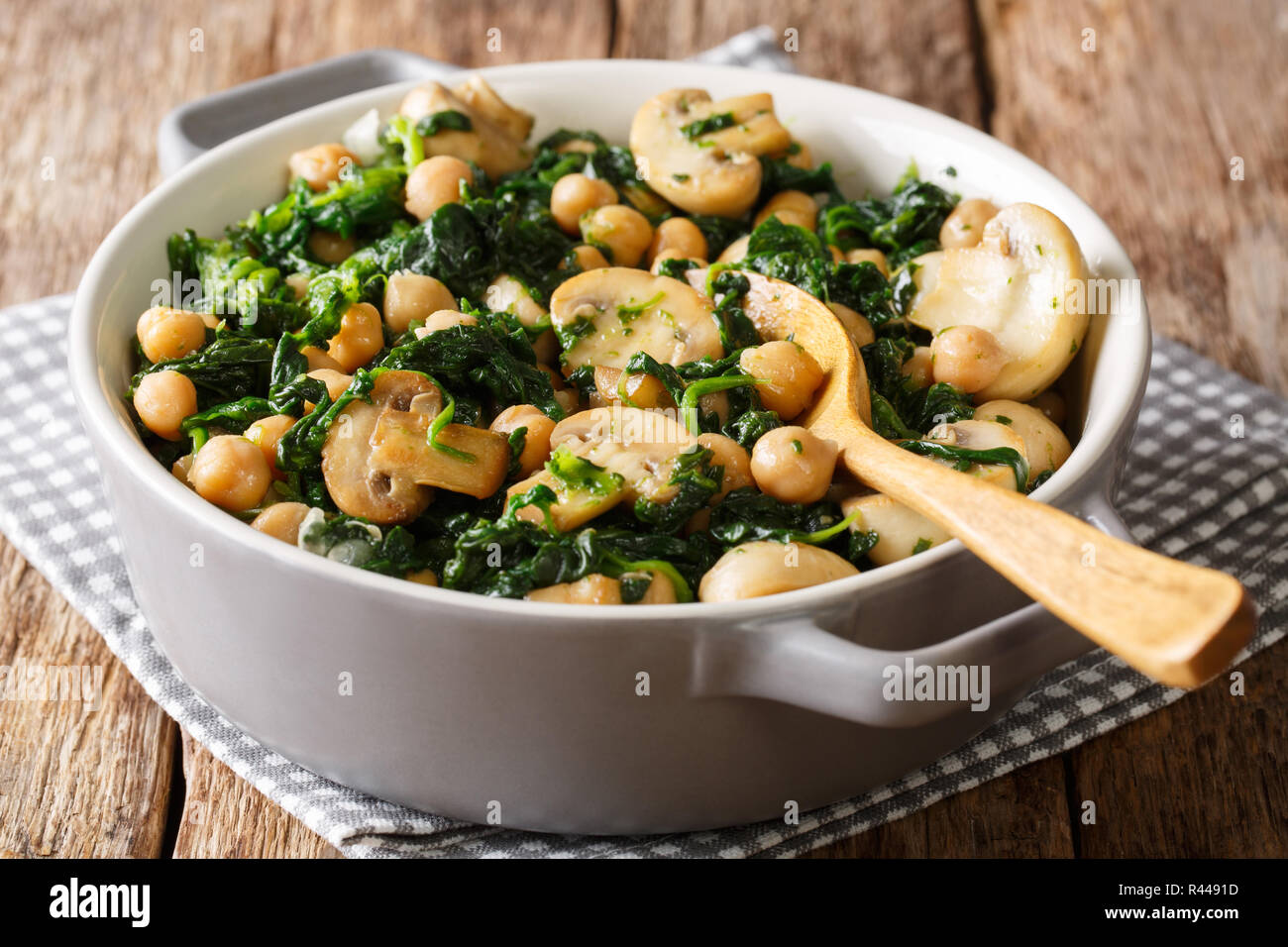 Cooked diet chickpeas with spinach and champignons close-up in a bowl on the table. horizontal Stock Photo