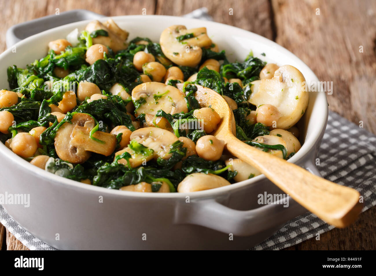 Healthy vegetarian food of chickpeas with spinach and mushrooms close-up in a bowl on the table. horizontal Stock Photo