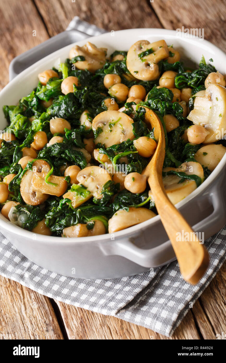 Stew of chickpeas with spinach and mushrooms close-up in a bowl on the table. vertical Stock Photo