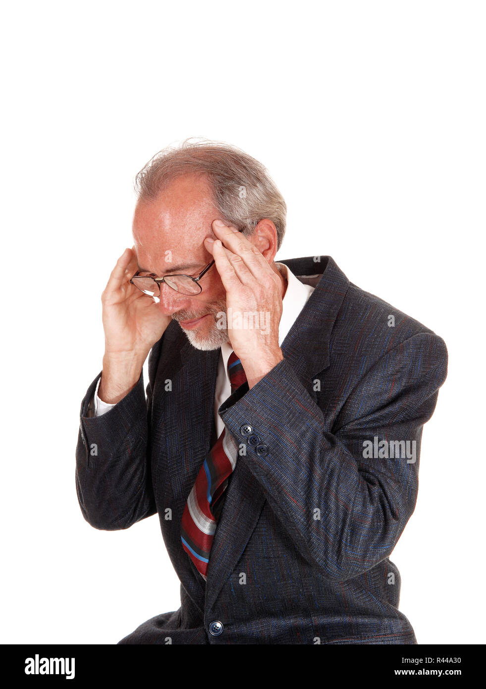 Older man in suit with headache. - Stock Image