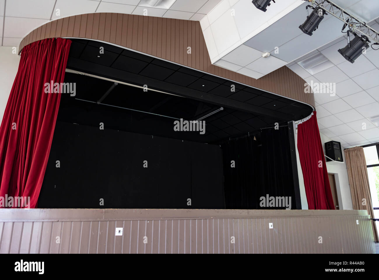 Wide shot of an indoor black stage with red curtains and spot lights hung on the ceiling, surrounded by wooden panels. - Stock Image
