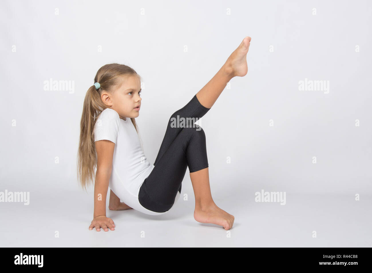 An aspiring gymnast trying to pull his left foot resting on the hands and fingers of the right foot - Stock Image