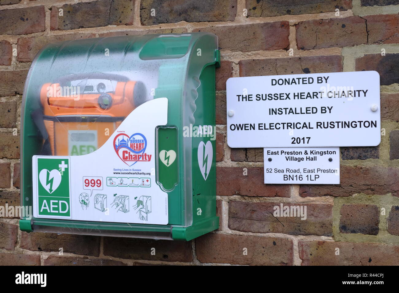 Public access defibrillator attached to the wall of village hall in East Preston, West Sussex, UK - Stock Image
